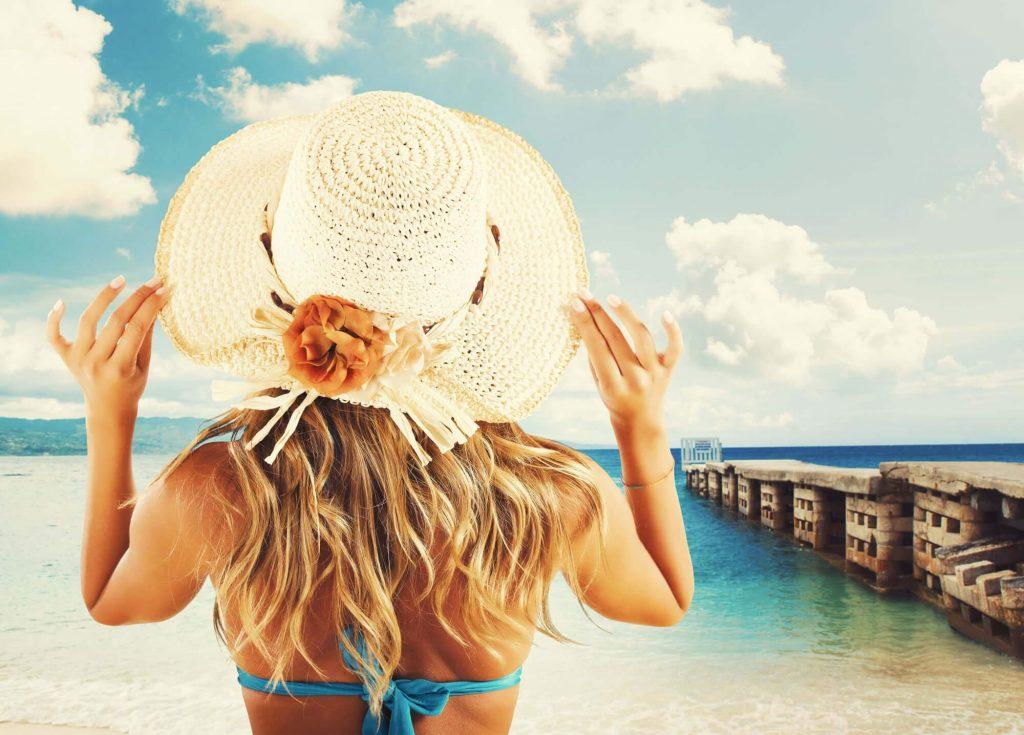 girl-holding-hat-on-beach